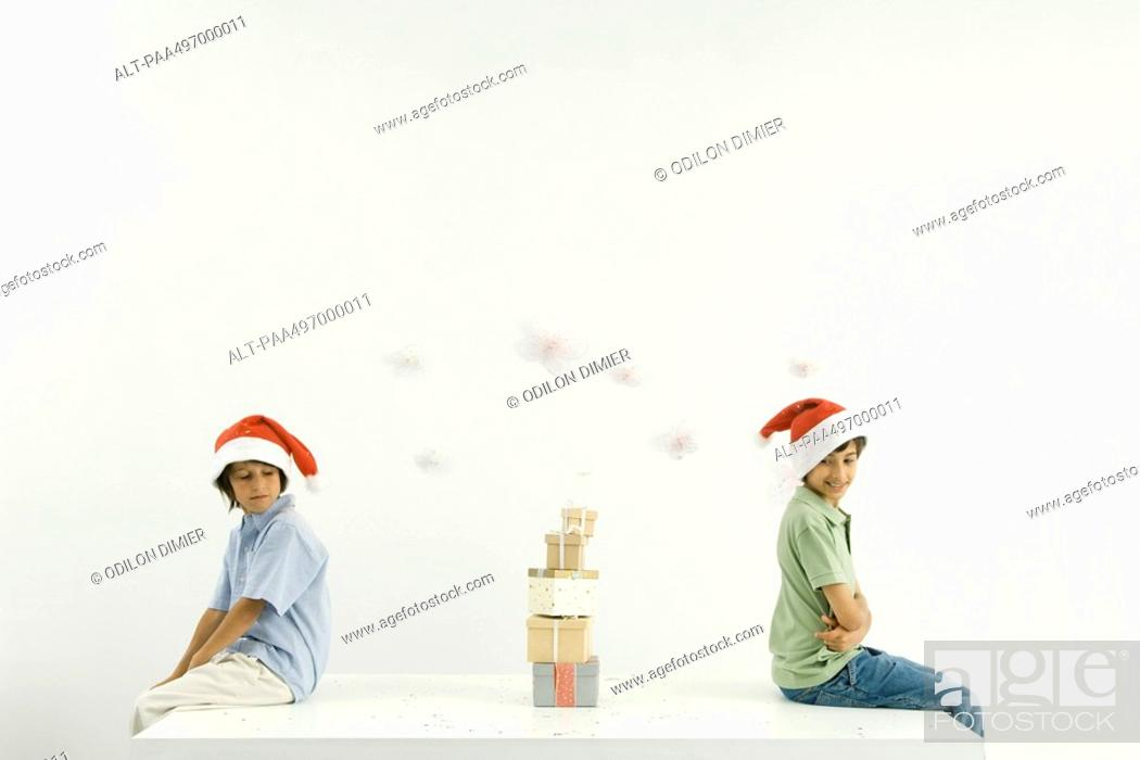 Stock Photo: Two brothers sitting back to back, Christmas gifts stacked between them, both wearing Santa hats.