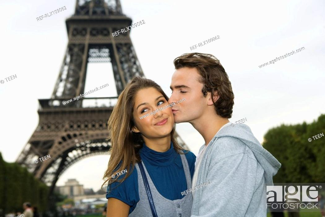 Stock Photo: Young couple kissing in front of Eiffel tower, Paris, France.