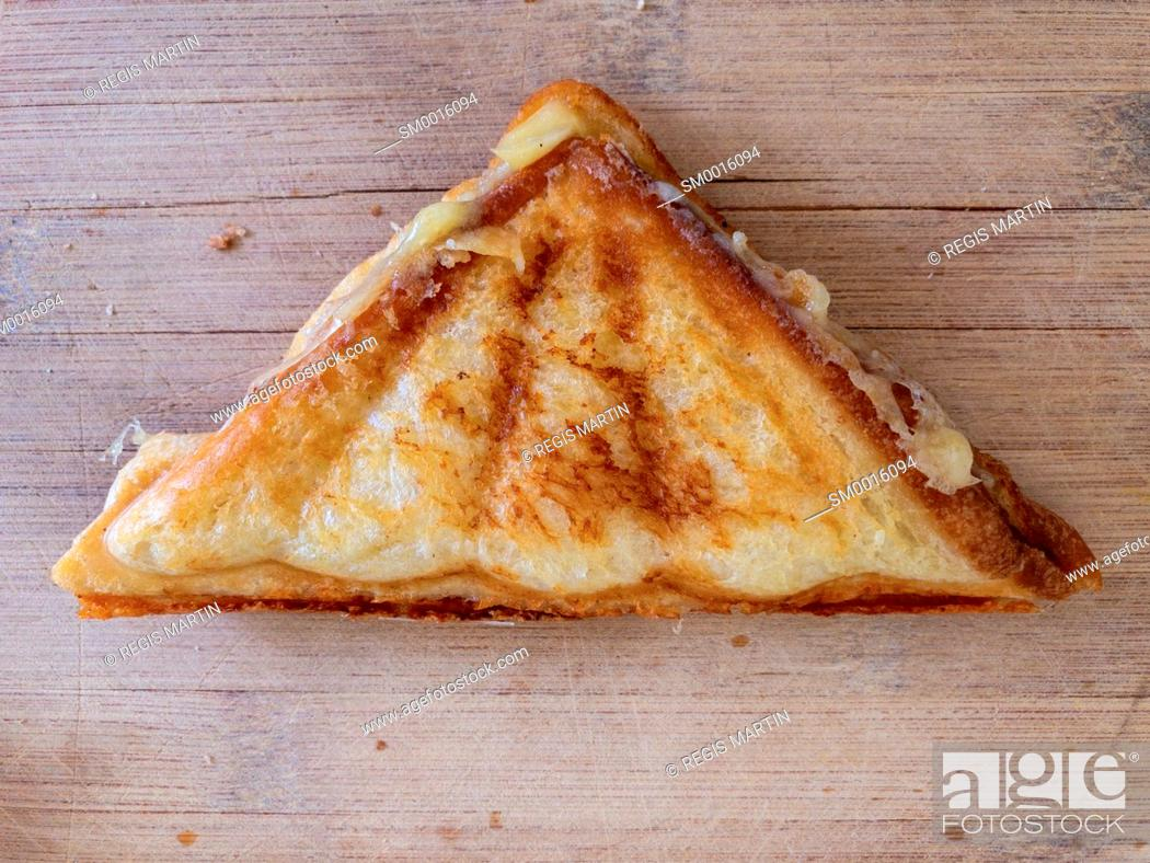 Stock Photo: toasted sandwich on a wooden cutting board.