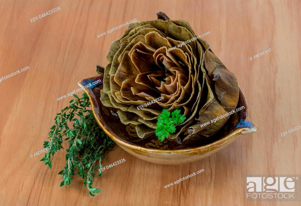 Imagen: Boiled artichokes with thyme on the wooden background.