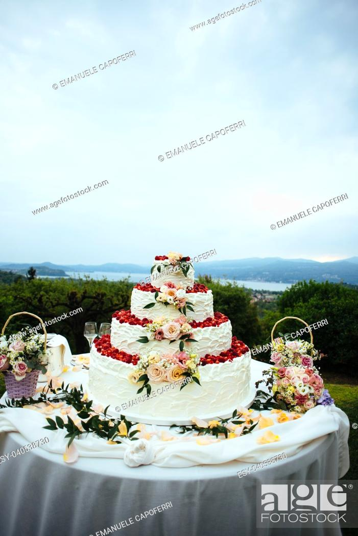 Stock Photo: cream and strawberries wedding cake outdoors in the garden decorated with flowers and rose petals.