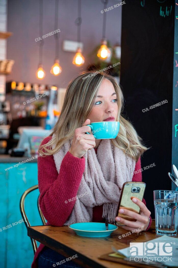Stock Photo: Woman sitting in cafe, holding smartphone, drinking coffee.