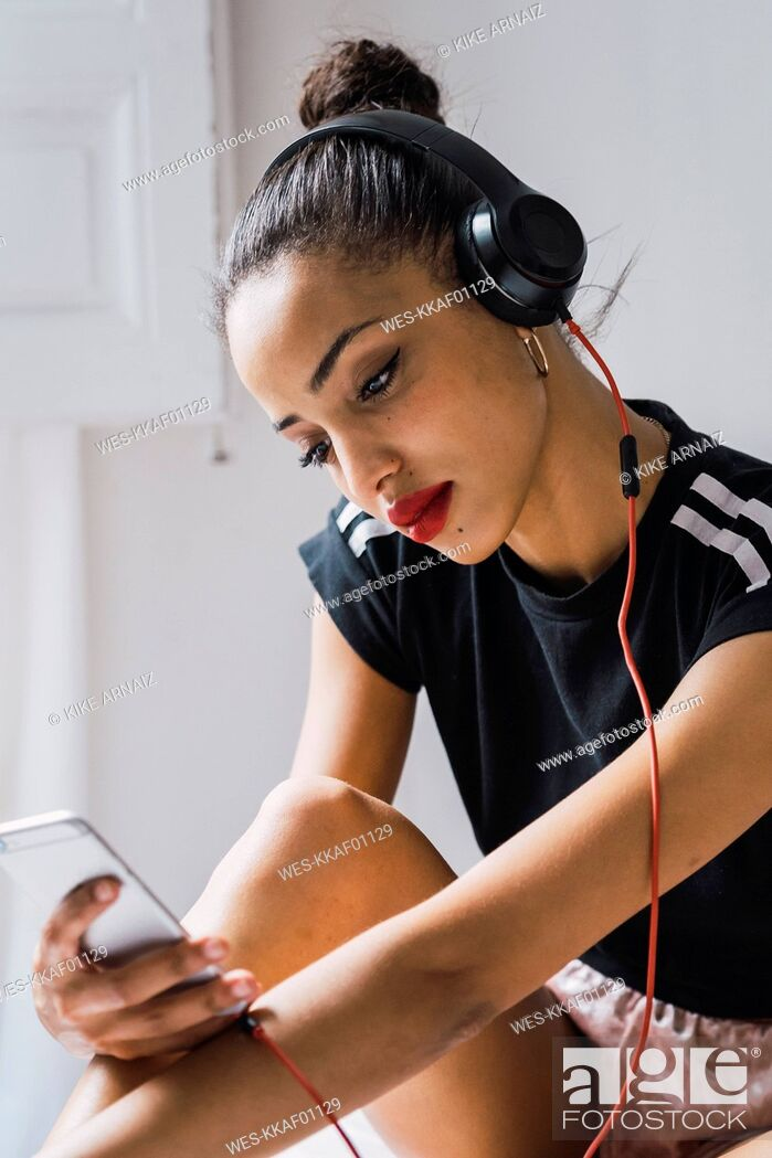 Stock Photo: Beautiful young woman sitting down wearing headphones looking at cell phone.