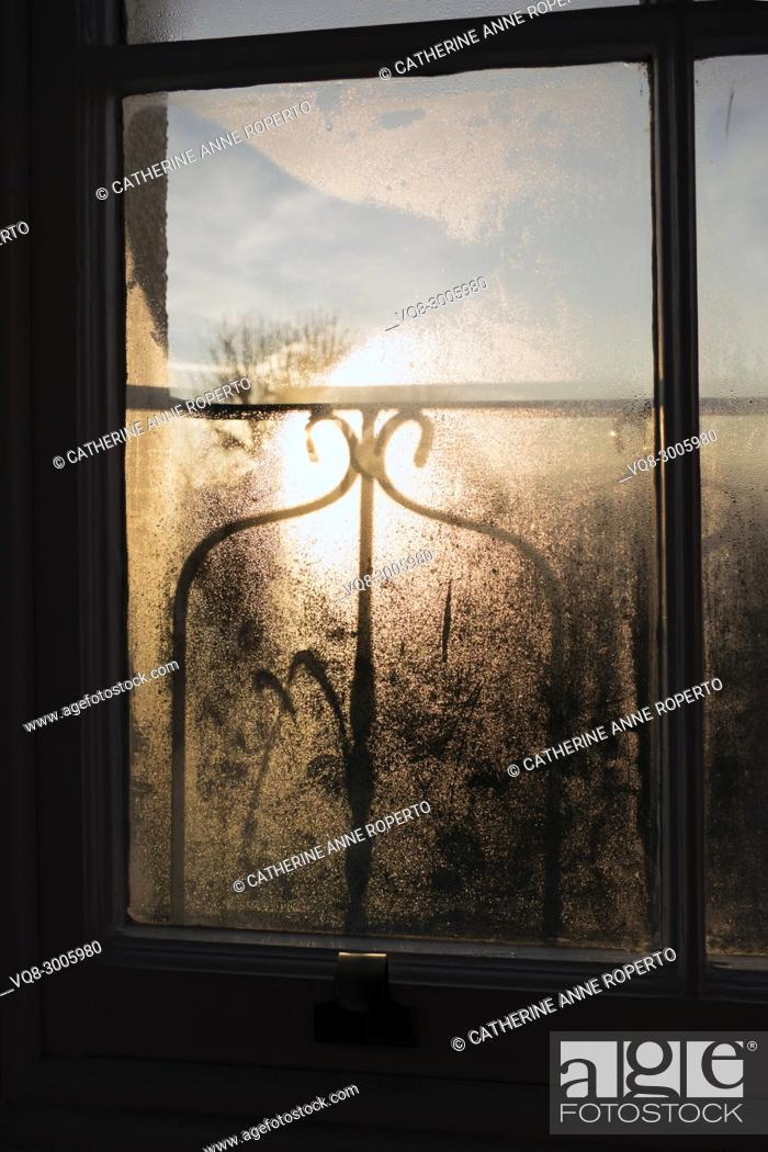 Stock Photo: Sunrise and shadows through a misty window pane and decorative ironwork balcony over the harbour, Hotwells, Bristol.