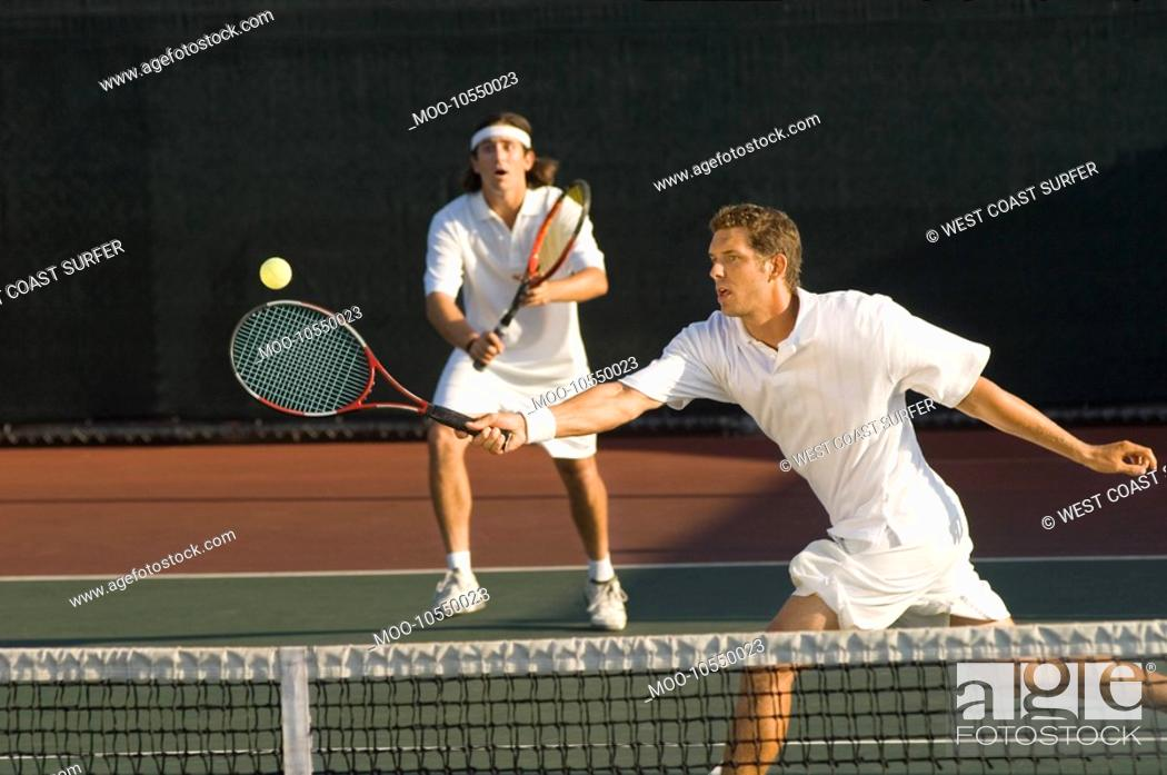 Stock Photo: Tennis Player stretching Swinging at Ball near tennis net doubles partner standing behind.