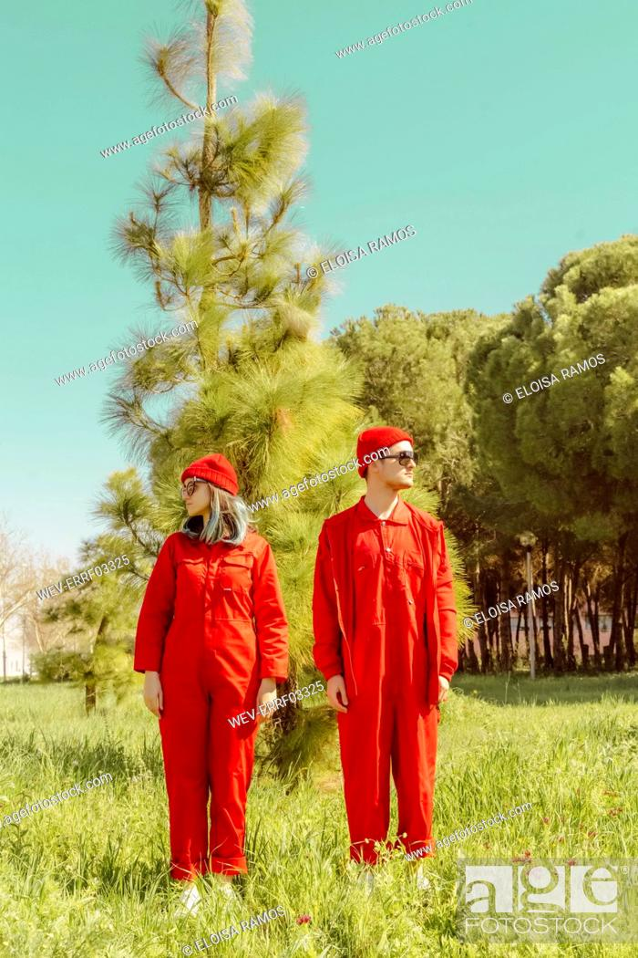 Stock Photo: Young couple wearing red overalls and hats standing on a meadow looking around.