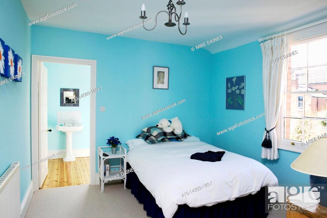 agefotostock & A modern bedroom with bright blue walls bed white curtains and en ...