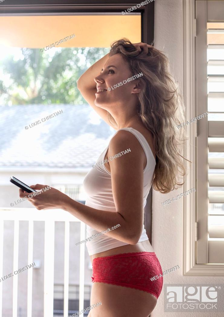 Stock Photo: Beautiful woman with hand in hair using mobile phone while standing at home.