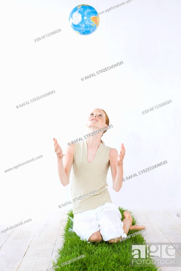 Stock Photo: young woman throwing up globe.