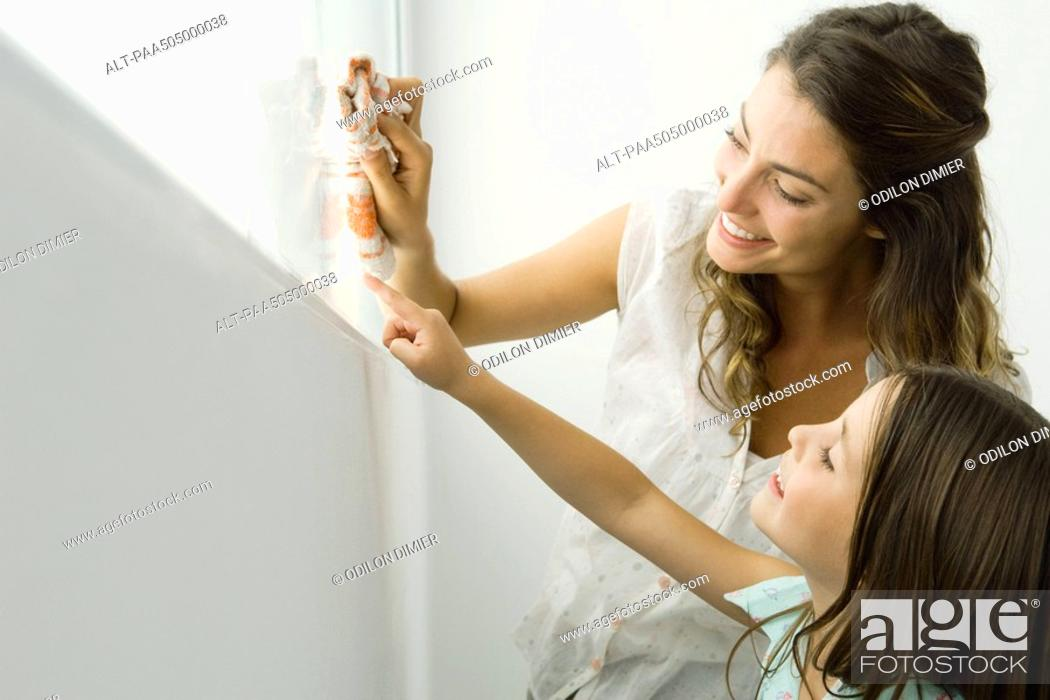 Stock Photo: Mother cleaning window, daughter pointing out another spot, both smiling.