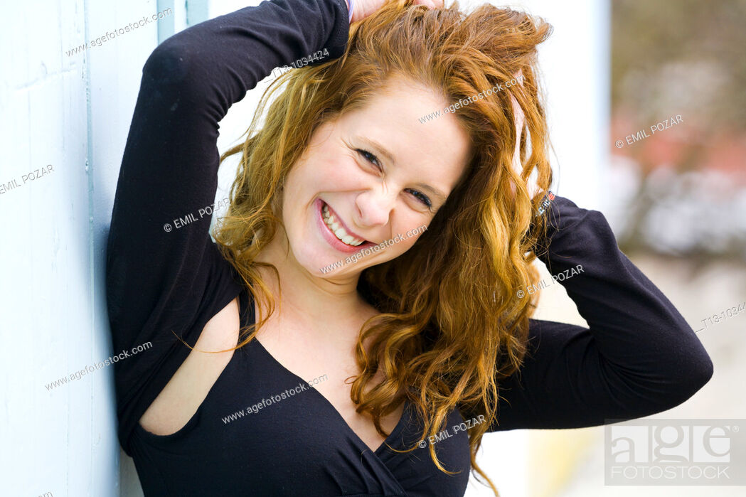 Stock Photo: Happy and holding hair attractive young woman portrait.