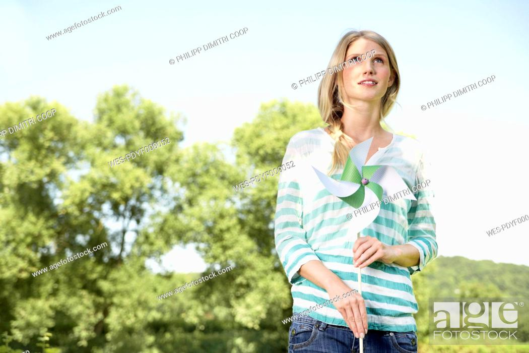 Stock Photo: Germany, Cologne, Young woman holding paper windmill, smiling.