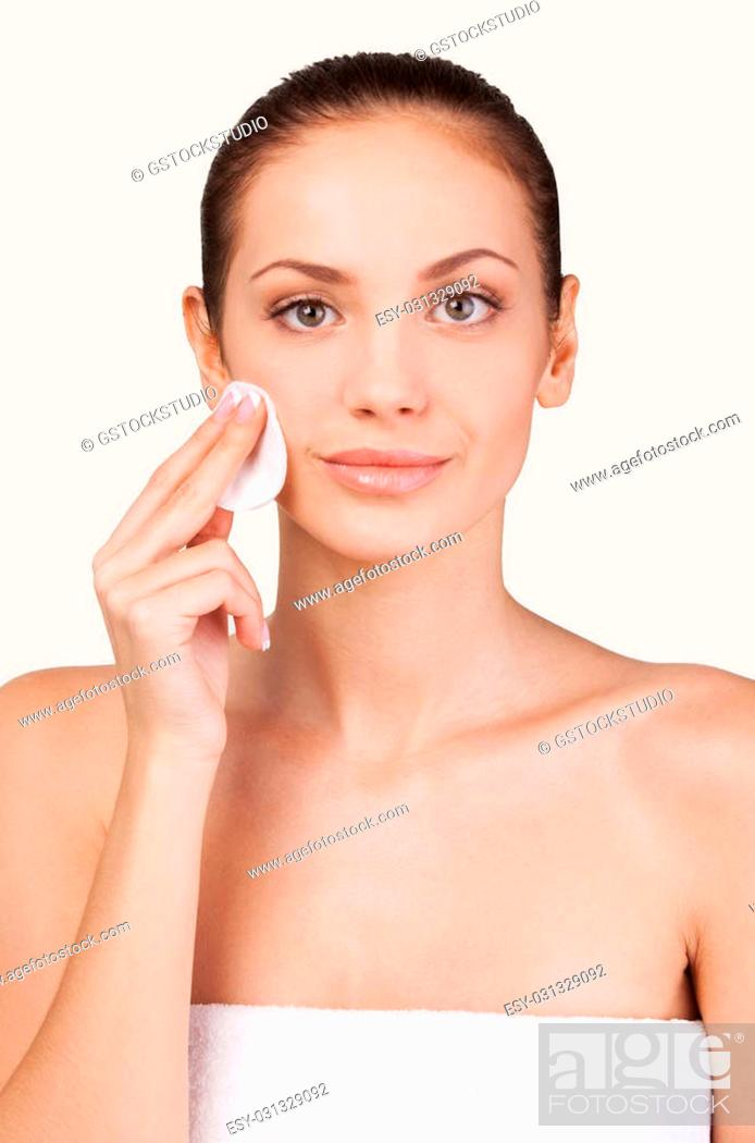 Stock Photo: Face care. Portrait of cheerful young shirtless woman smiling at camera and touching face while standing against grey background.