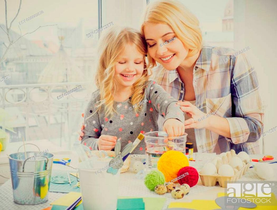 Stock Photo: Cheerful mother and her daughter painting and decorating easter eggs.