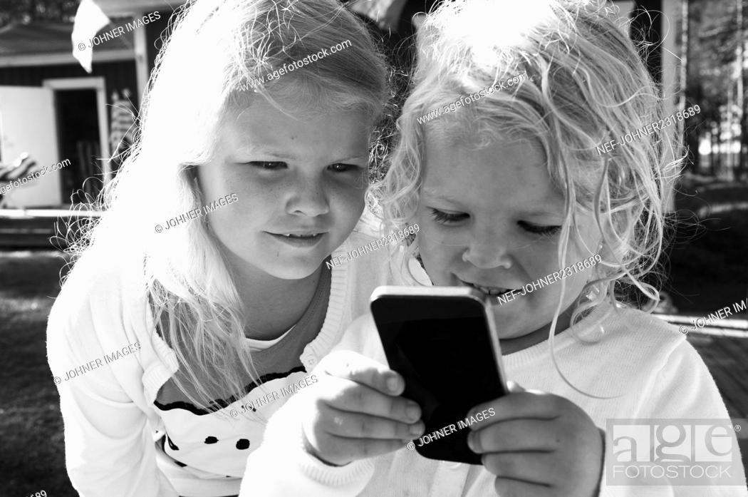 Stock Photo: Girls using cell phone.