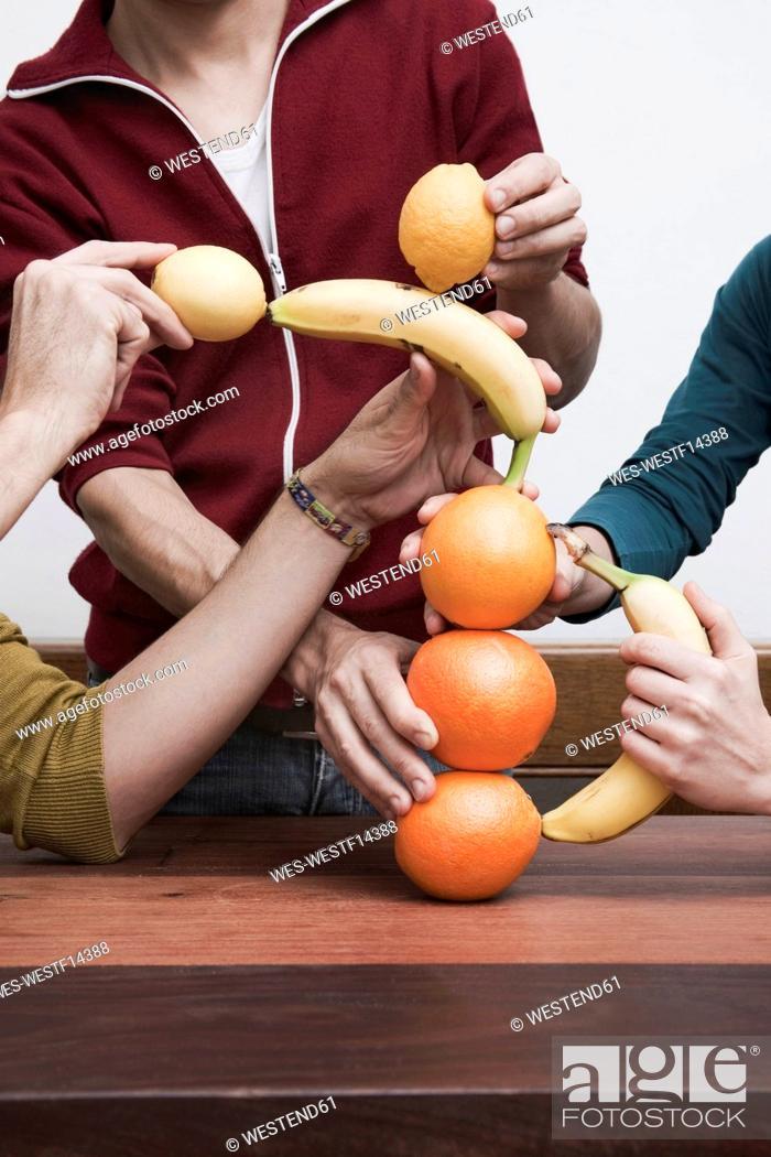 Stock Photo: Men and women balancing fruits.