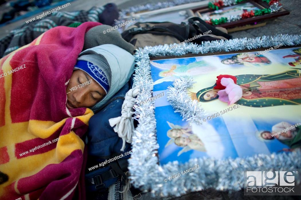 Stock Photo: A pilgrim sleeps in the street by an image of the Our Lady of Guadalupe virgin in Mexico City, December 11, 2010  Hundreds of thousands of Mexican pilgrims.