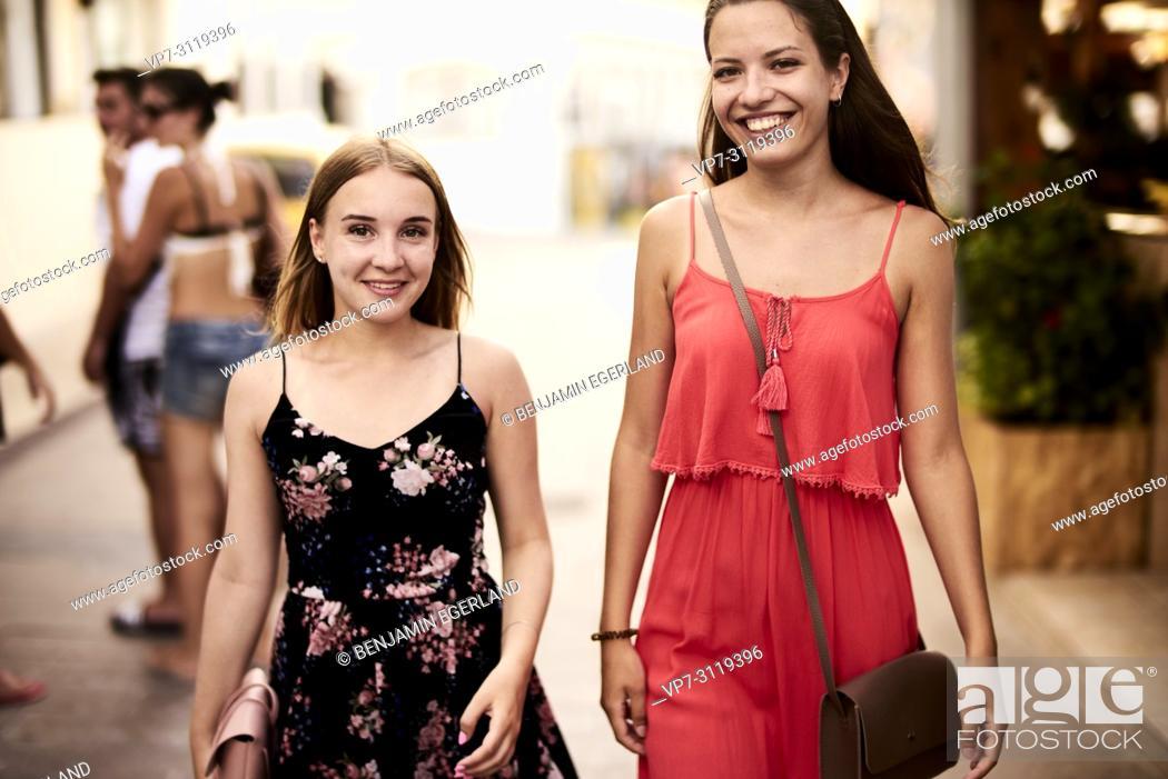 Photo de stock: two women walking in streets of holiday destination Chersonisoss, Crete, Greece.