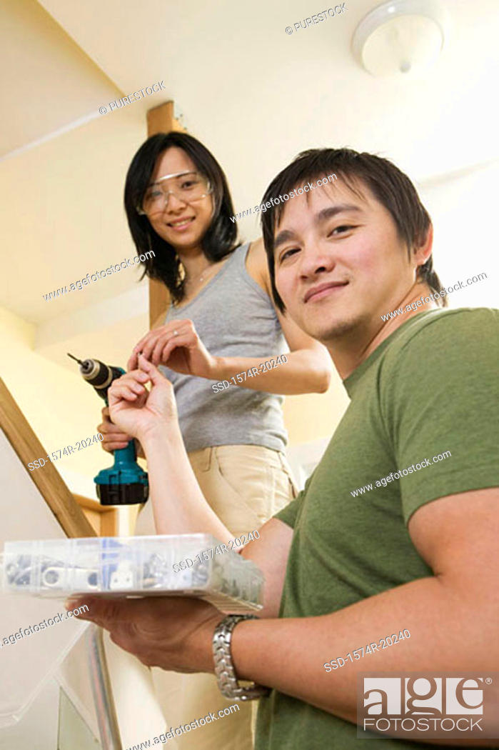 Stock Photo: Low angle view of a young man giving a drill bit to a young woman.