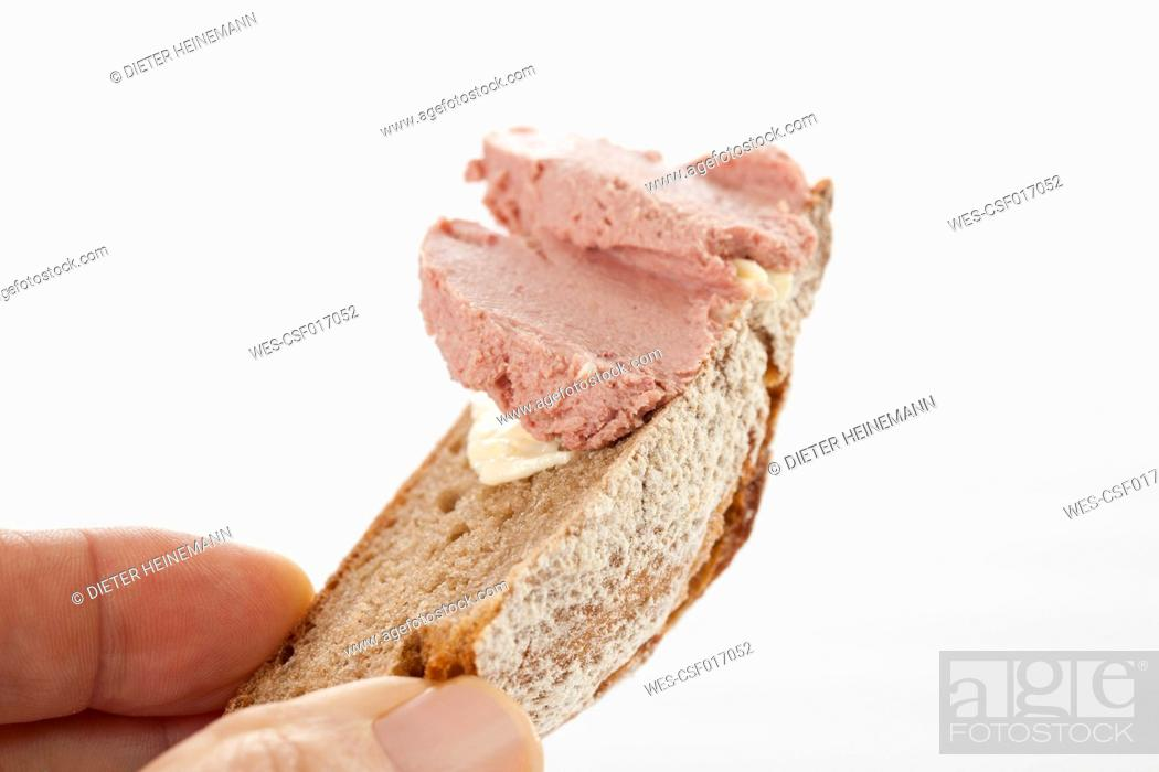 Stock Photo: Human hand holding bread with sausage, close up.