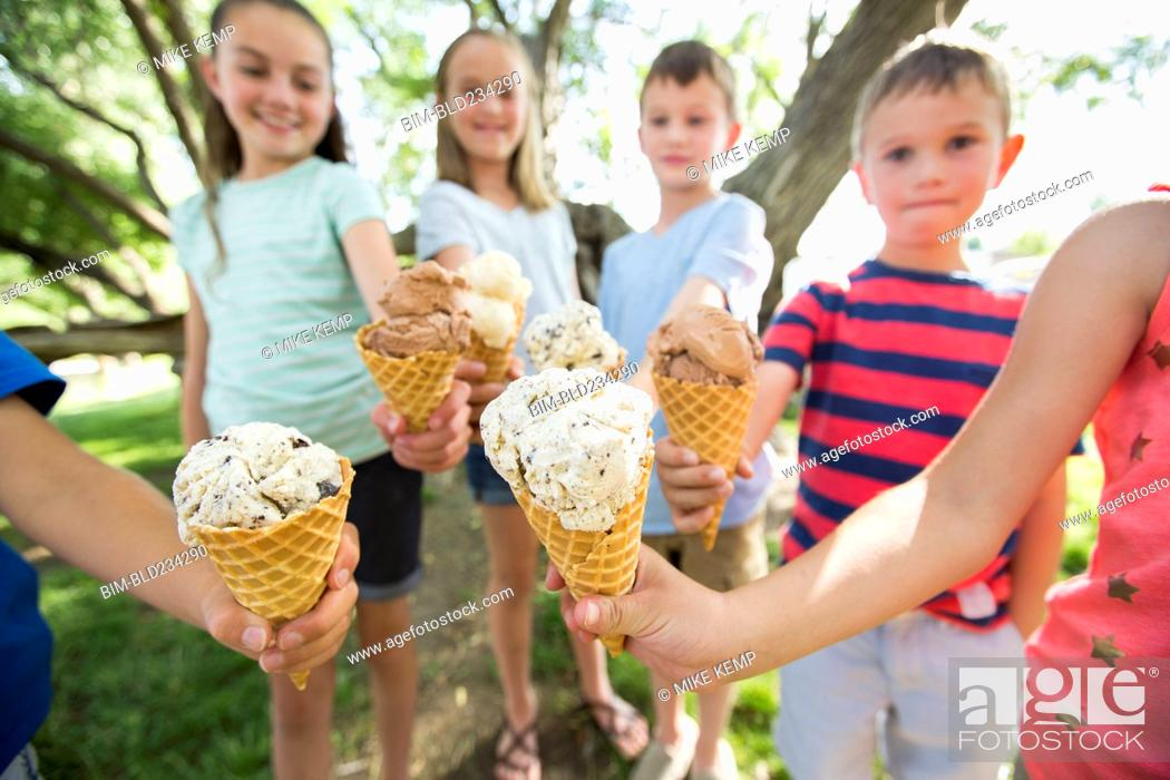 Stock Photo: Caucasian boys and girls showing ice cream cones.