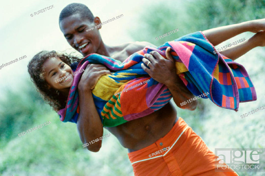 Stock Photo: Father carrying his daughter on the beach.