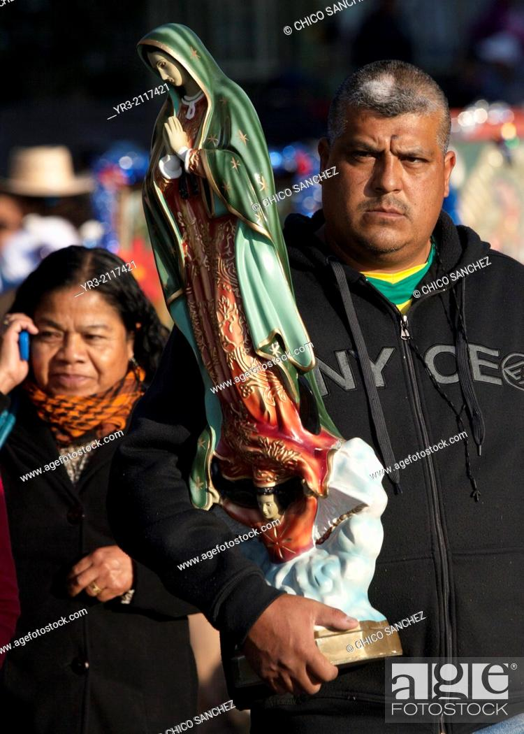 Stock Photo: A pilgrim holds an image of the Virgin of Guadalupe at the pilgrimage to Our Lady of Guadalupe Basilica in Mexico City, Mexico, December 10, 2013.