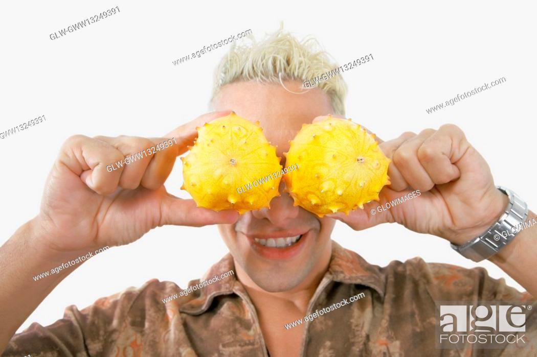 Stock Photo: Close-up of a young man holding two kawani fruits on his eyes.