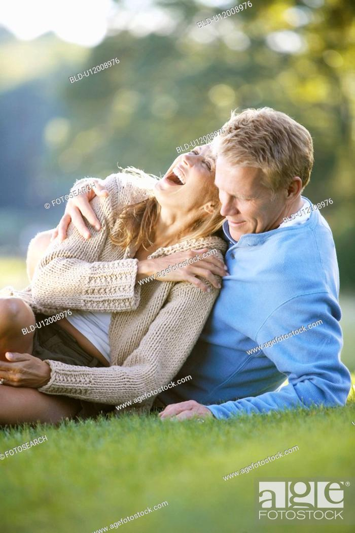 Stock Photo: Couple lying on grass and laughing.