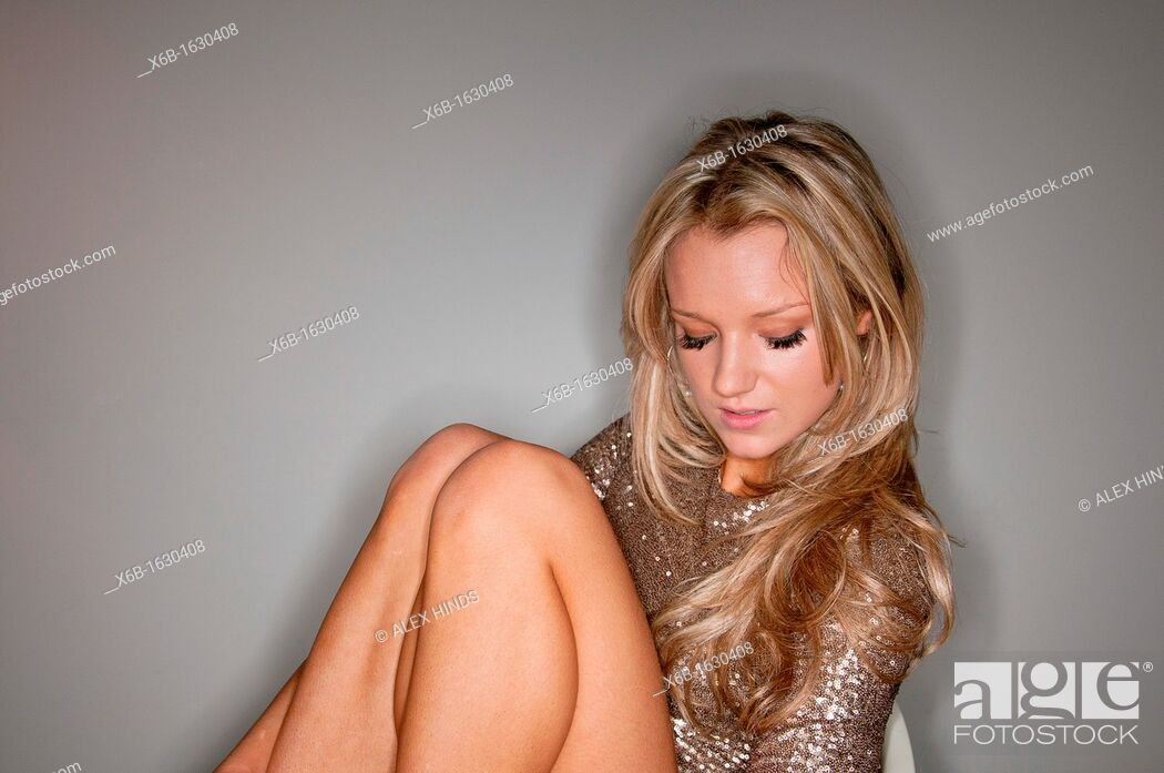 Stock Photo: Young woman portrait, 18-25 years, posing in gold sequin party dress.