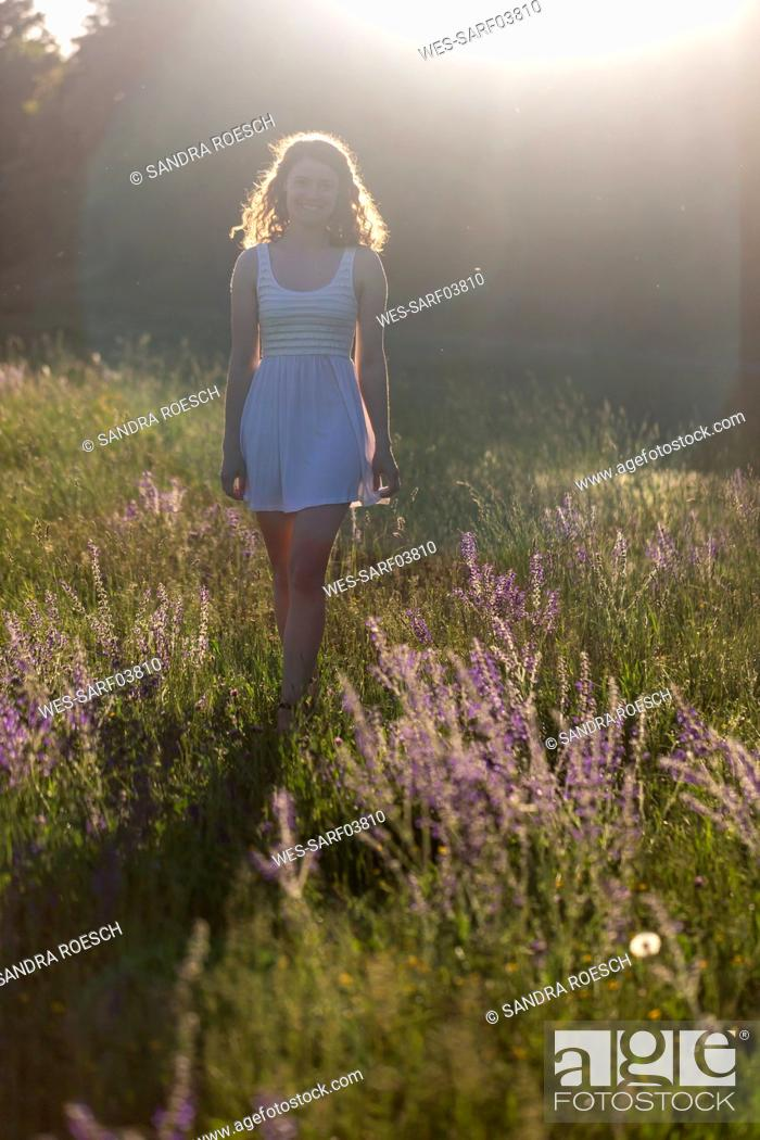 Photo de stock: Young woman walking on flower meadow in the evening light.