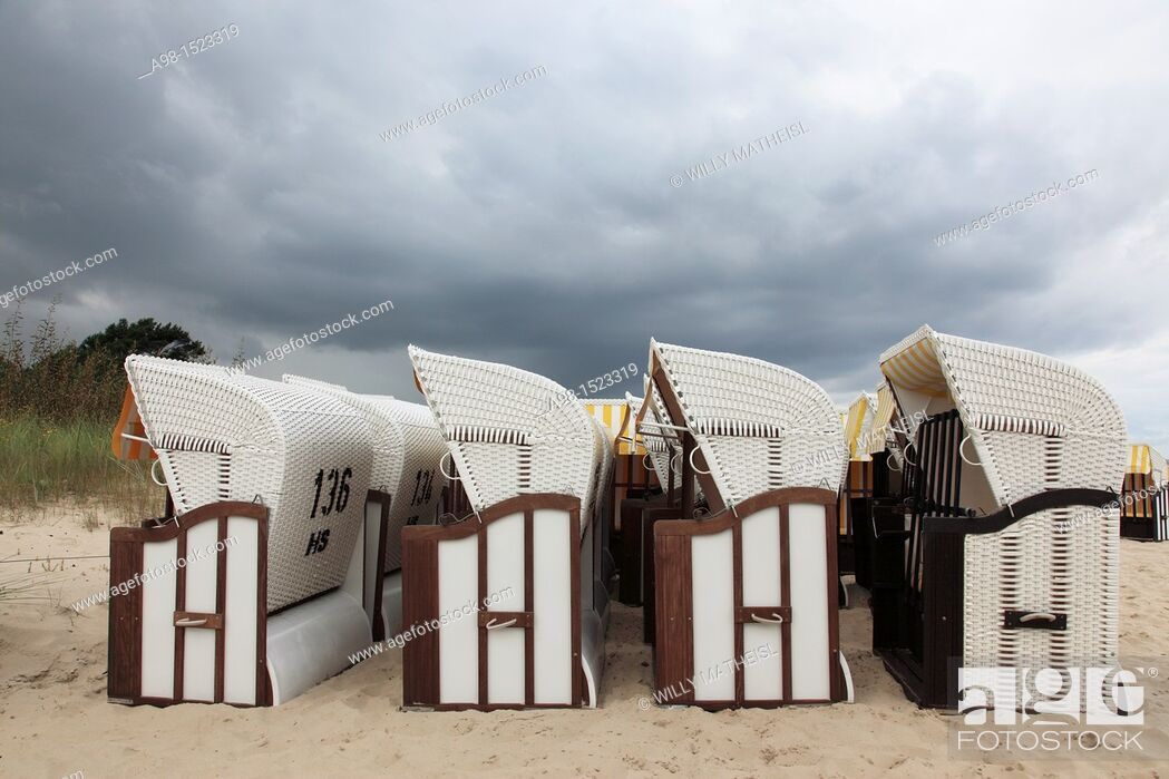 Stock Photo: rain clouds above roofed wicker beach chair at the sandy coast of the isle of Usedom, Western Pomerania, Germany, Europe.