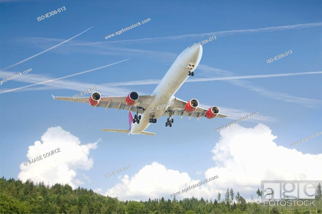Stock Photo: Airplane above a forest.