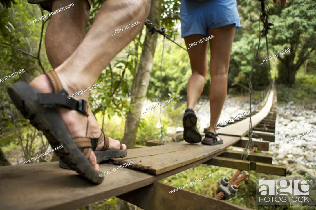 Stock Photo: Man and woman walking across footbridge, low section, rear view.
