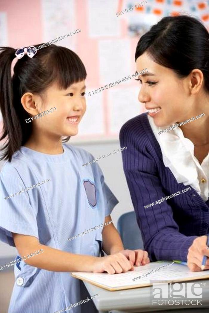 Stock Photo: Teacher Helping Student Working At Desk In Chinese School Classroom.