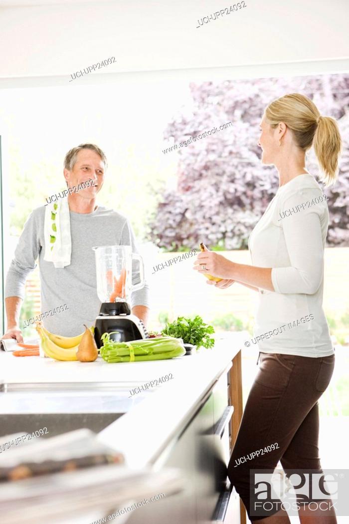 Stock Photo: Couple preparing health shake in kitchen.