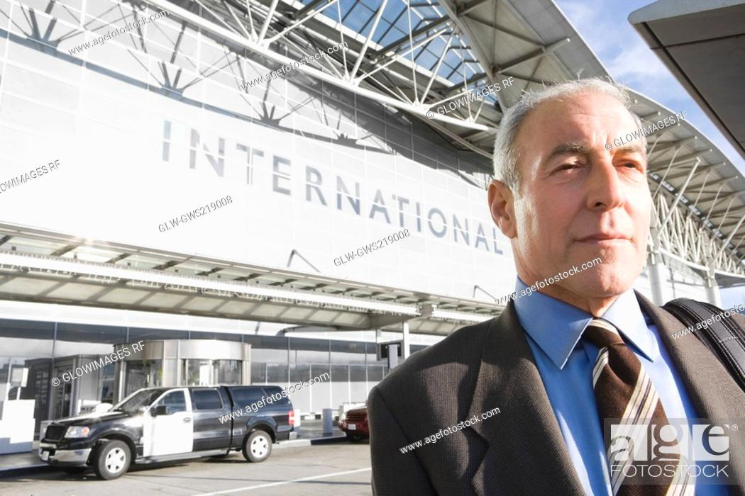 Stock Photo: Close-up of a businessman in front of an airport.