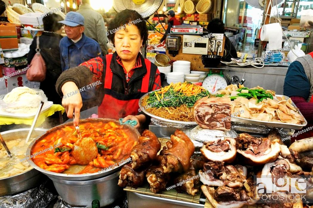 Imagen: korean food, woman cooking in a small restaurant, food stall in a market in Seoul, South Korea, Asia.