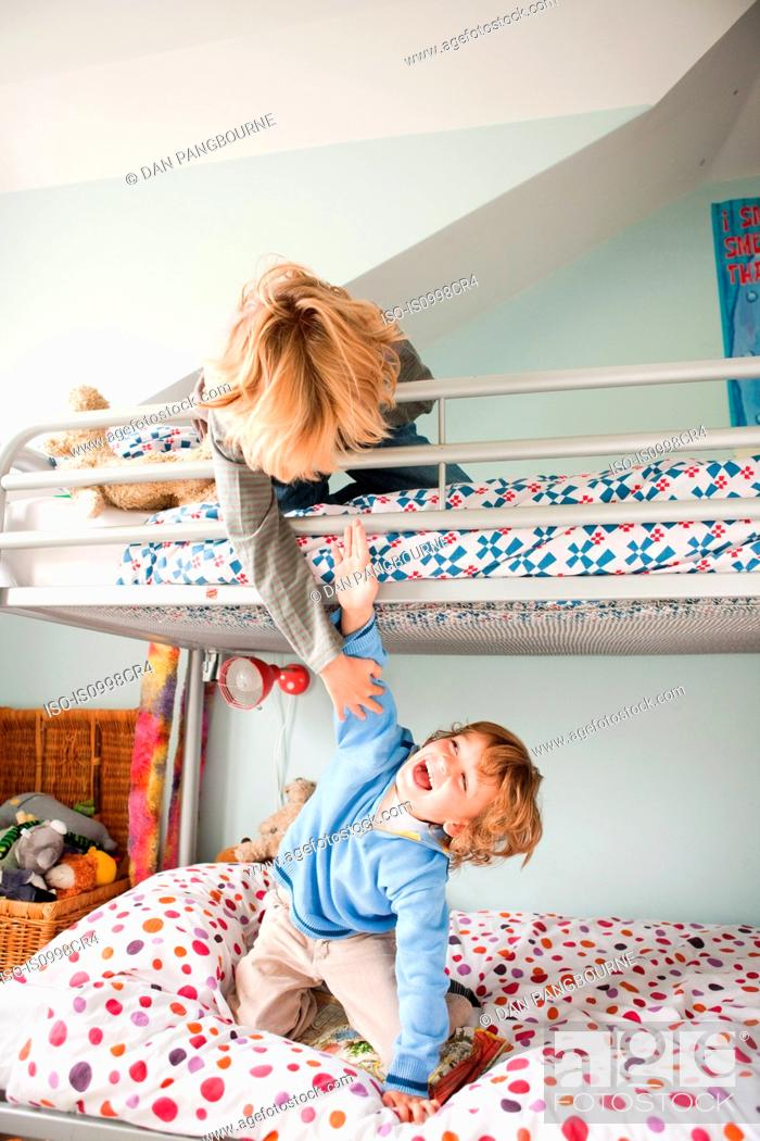 Stock Photo: Young boys playfighting on their bunk bed.