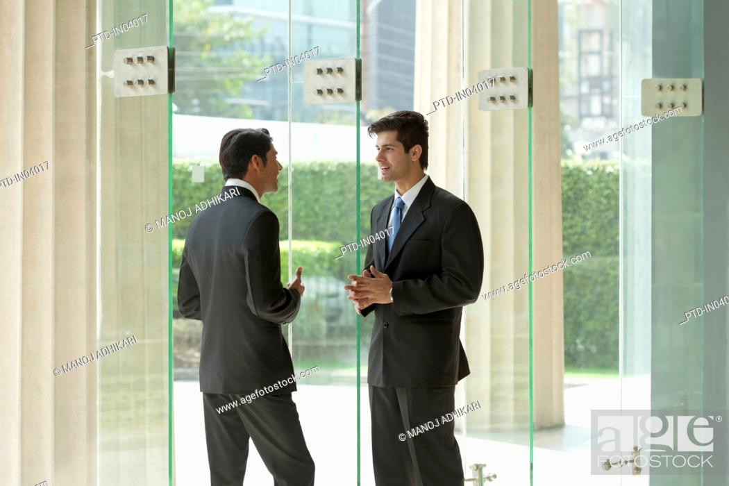 Stock Photo: India, Two businessmen talking in office lobby.