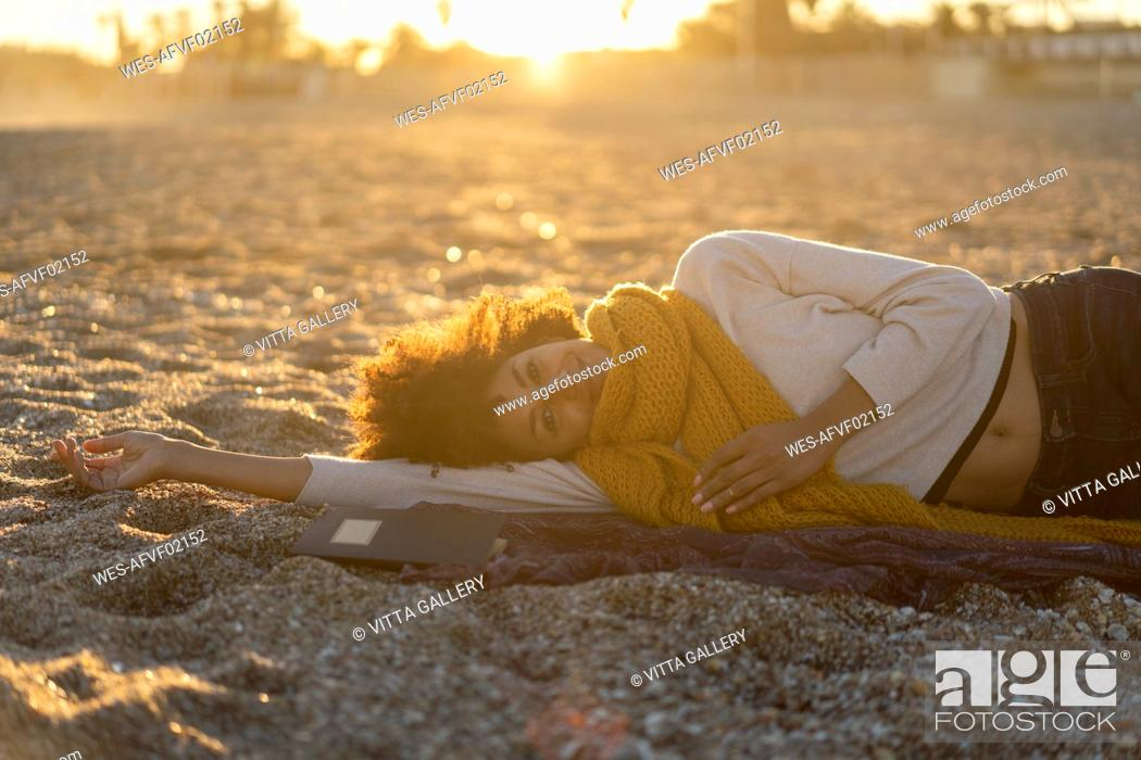 Stock Photo: Woman lying in the sand, relaxing on the beach.