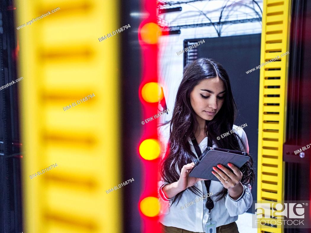Stock Photo: Mixed race technician using digital tablet in server room.