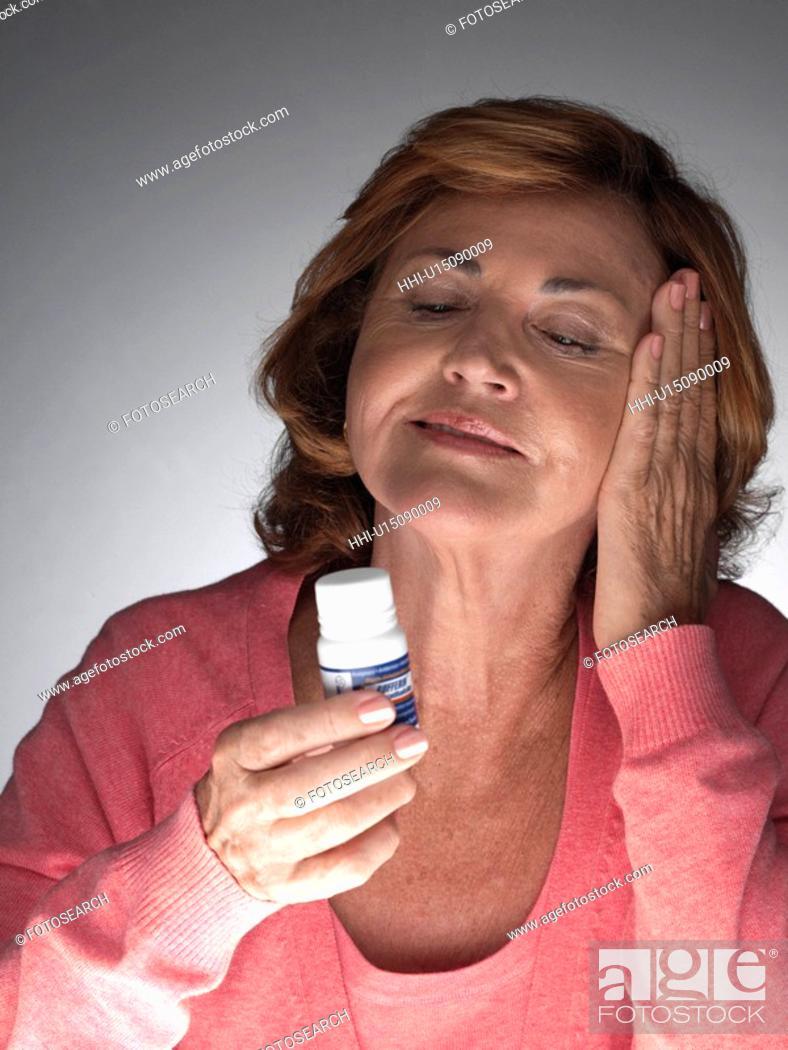 Stock Photo: Mature woman taking aspirin.