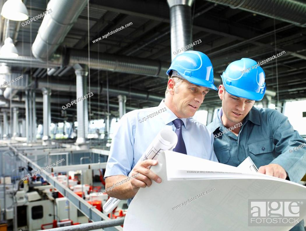 Stock Photo: Businessmen looking at blueprints in factory.