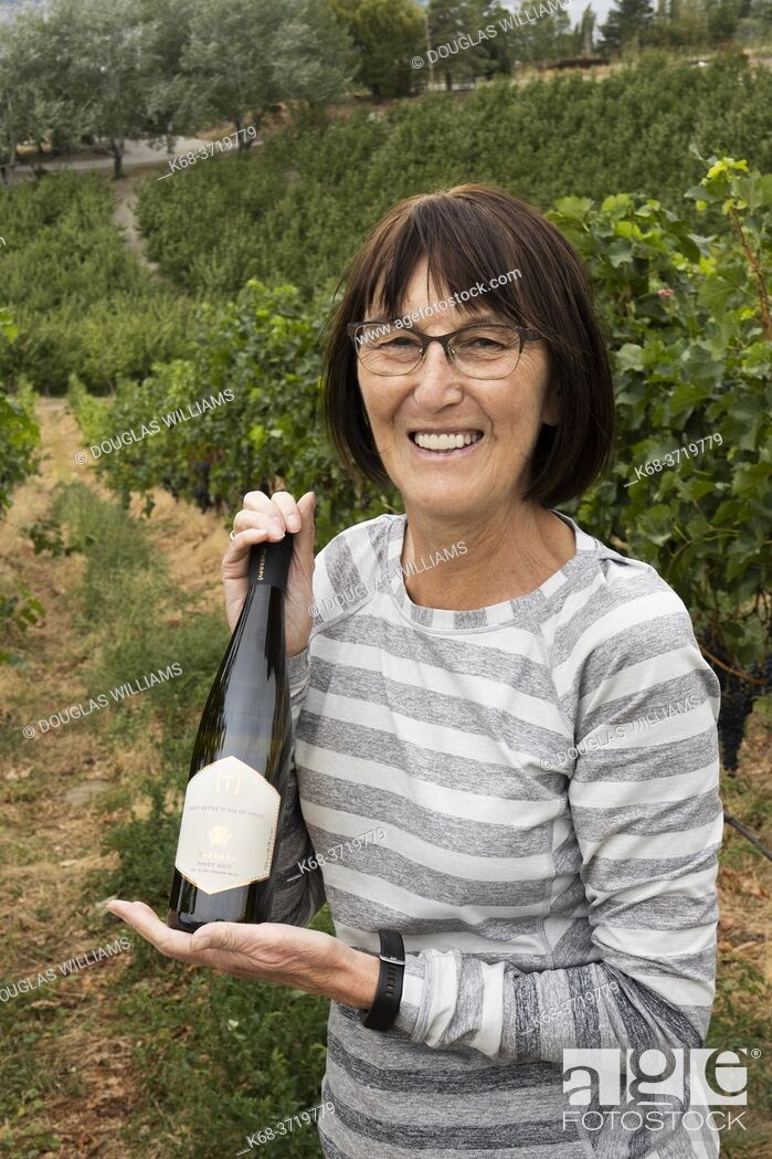 Stock Photo: Woman, 70, with bottle of wine from a vineyard in Naramata, BC, Canada.