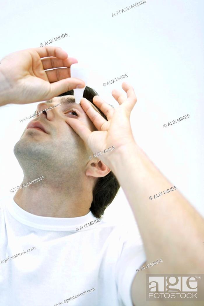 Stock Photo: Man applying eye drops, head back.