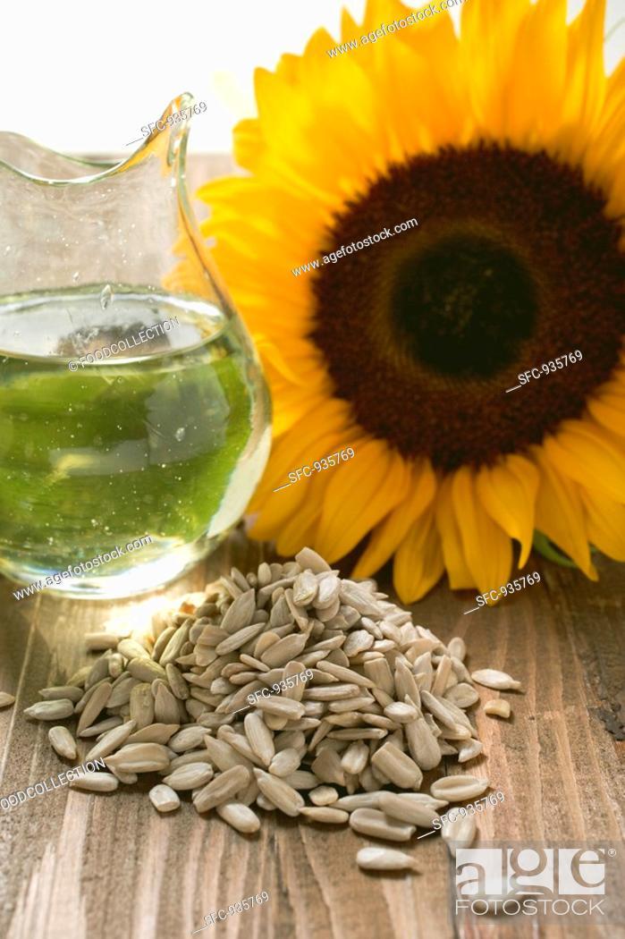 Stock Photo: Shelled sunflower seeds, sunflower oil and sunflower.
