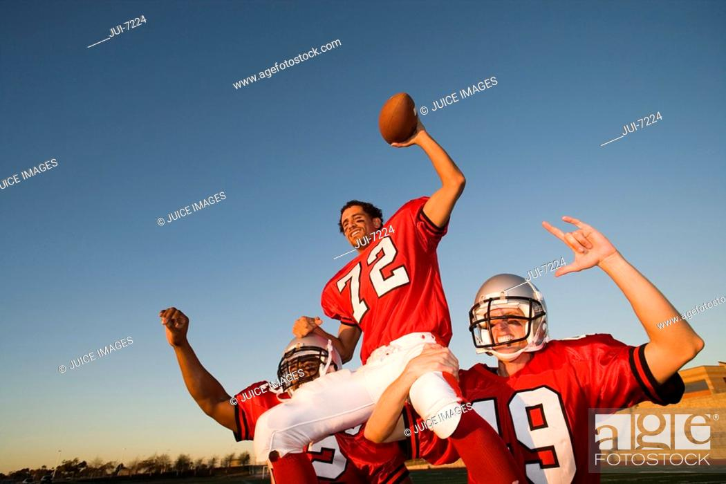 Stock Photo: American football players, in red football strips, celebrating victory post match, man being carried on teammatesÔÇÖ shoulders, smiling, low angle view.