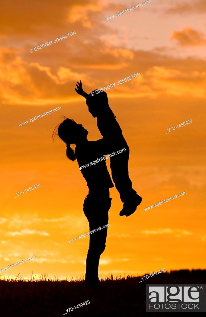 Stock Photo: A mother holds her little sun up in the air during sunset.