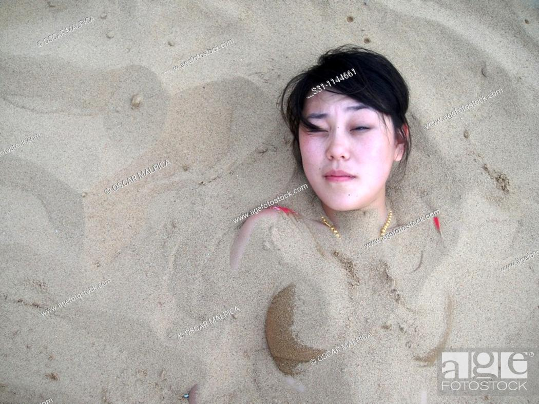 Stock Photo: asian woman buried in sand on a beach.